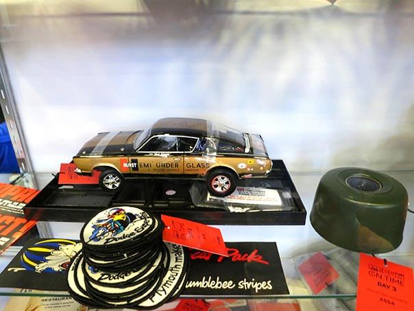 Small model car figure in a glass case.