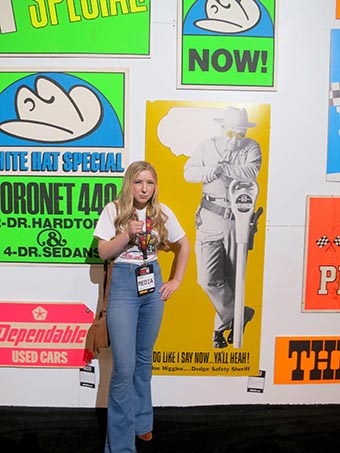 Young lady poses next to a poster of a police officer threatening to write a ticket