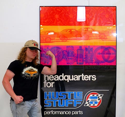 "Young man poses next to a large sign reading "" headquarters for hustle stuff""."