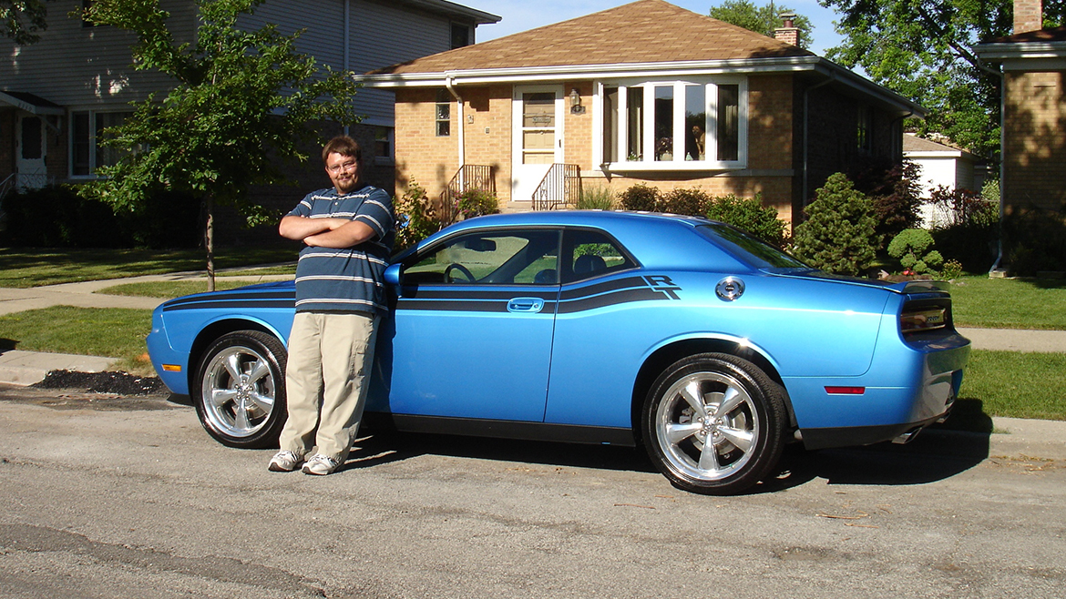 A man standing next to his 2009 Challenger R/T Classic in B5 Blue