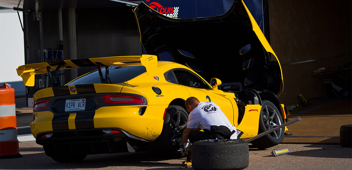 a man changing the tire on a yellow dodge viper