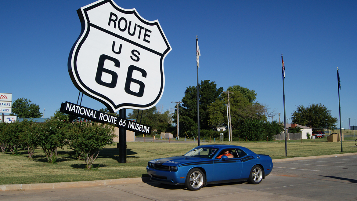 a man driving a 2009 Challenger R/T Classic in B5 Blue parked next to the route 66 sign