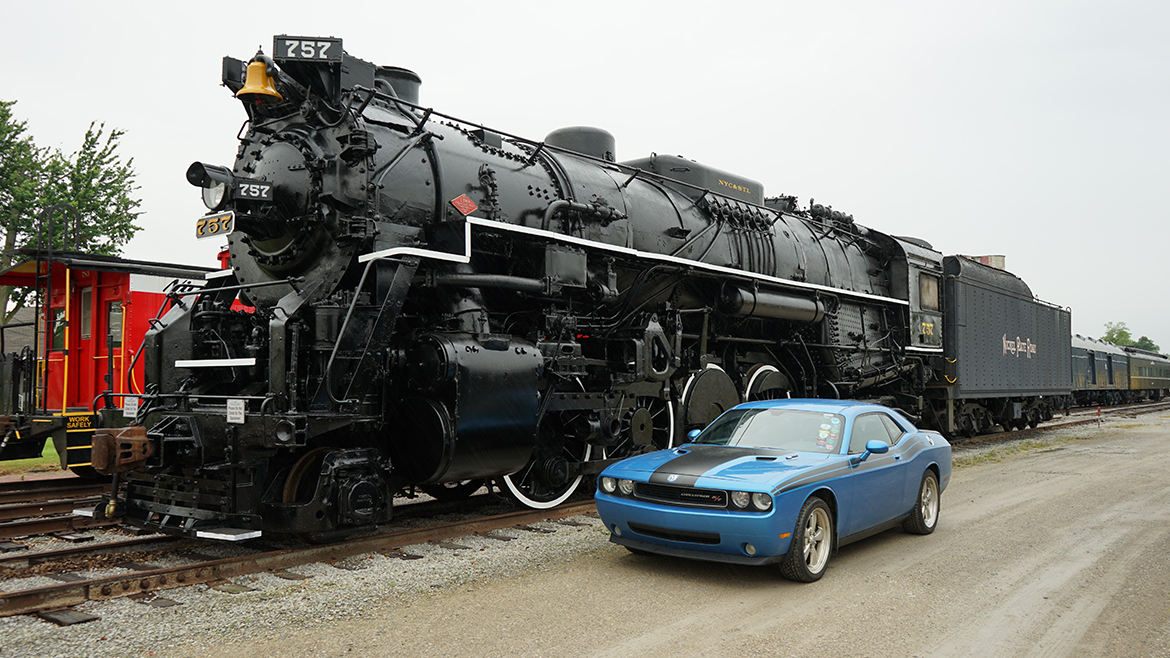 a 2009 Challenger R/T Classic in B5 Blue parked next to a black train on the railroad tracks