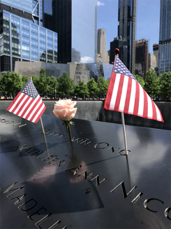 two flags and a rose on the edge of the nine eleven memorial