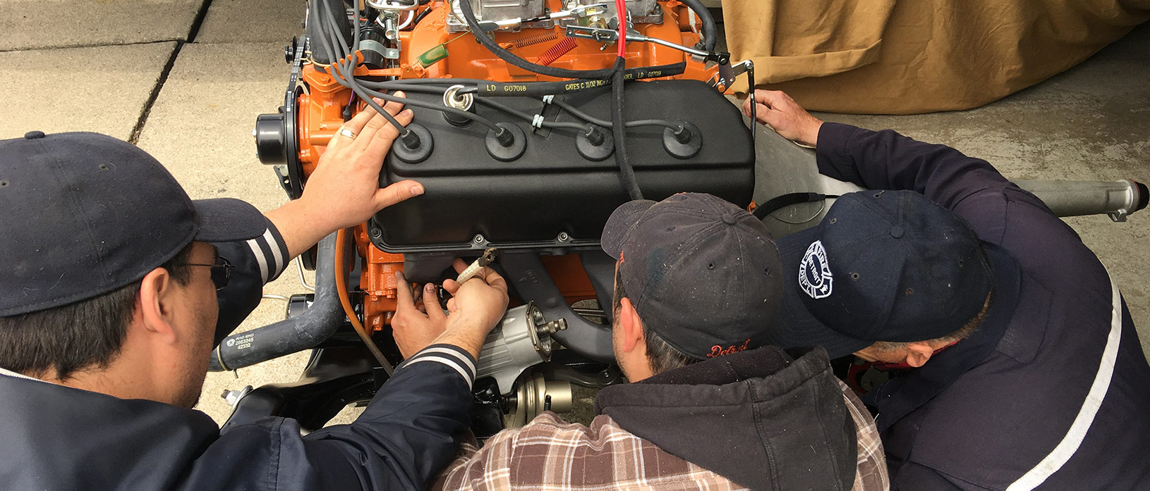 Michael, Erik, and Dave Belcarz work on an engine together.