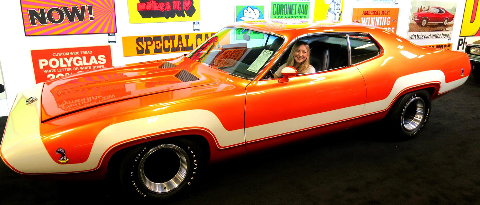 A young lady in an orange and white older vehicle at Steven Juliano's private collection.