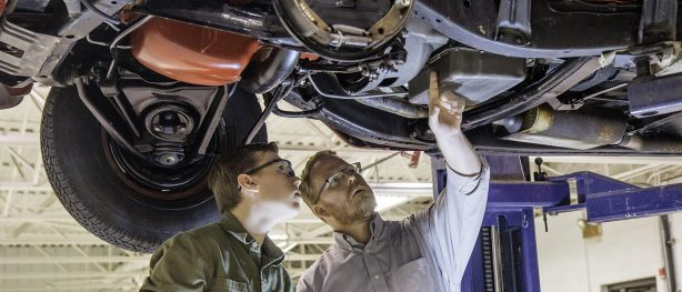 Two men examining the undercarriage of a car.