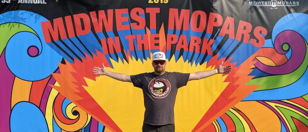 Bud Kleppe standing in front of Mopars in the Park sign