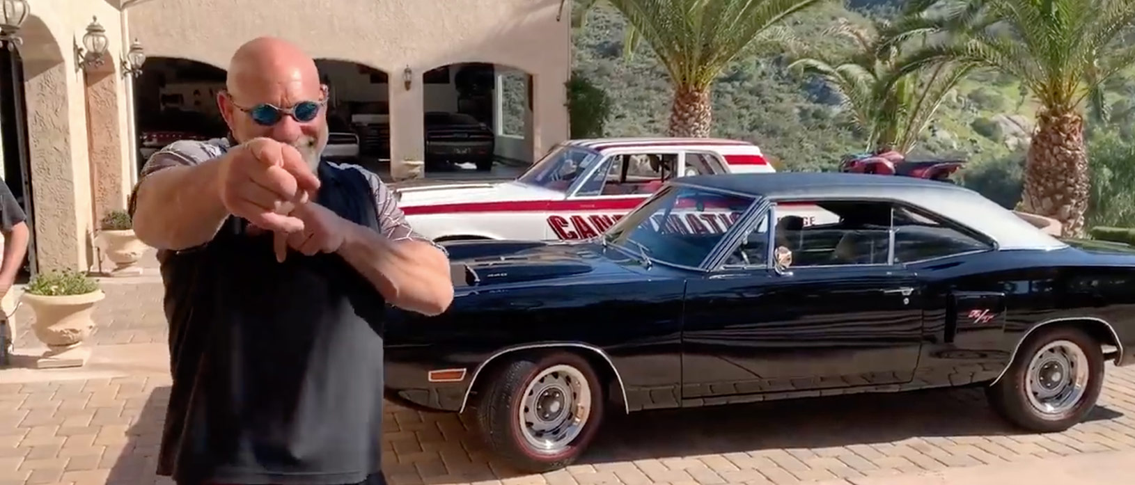 Bill Goldberg standing in front of his car collection outside of his garage at his home