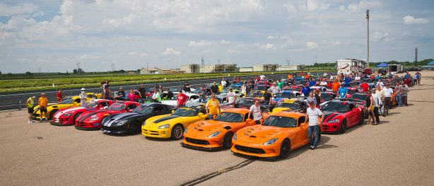 dodge vipers lines up and all their owners standing next to them