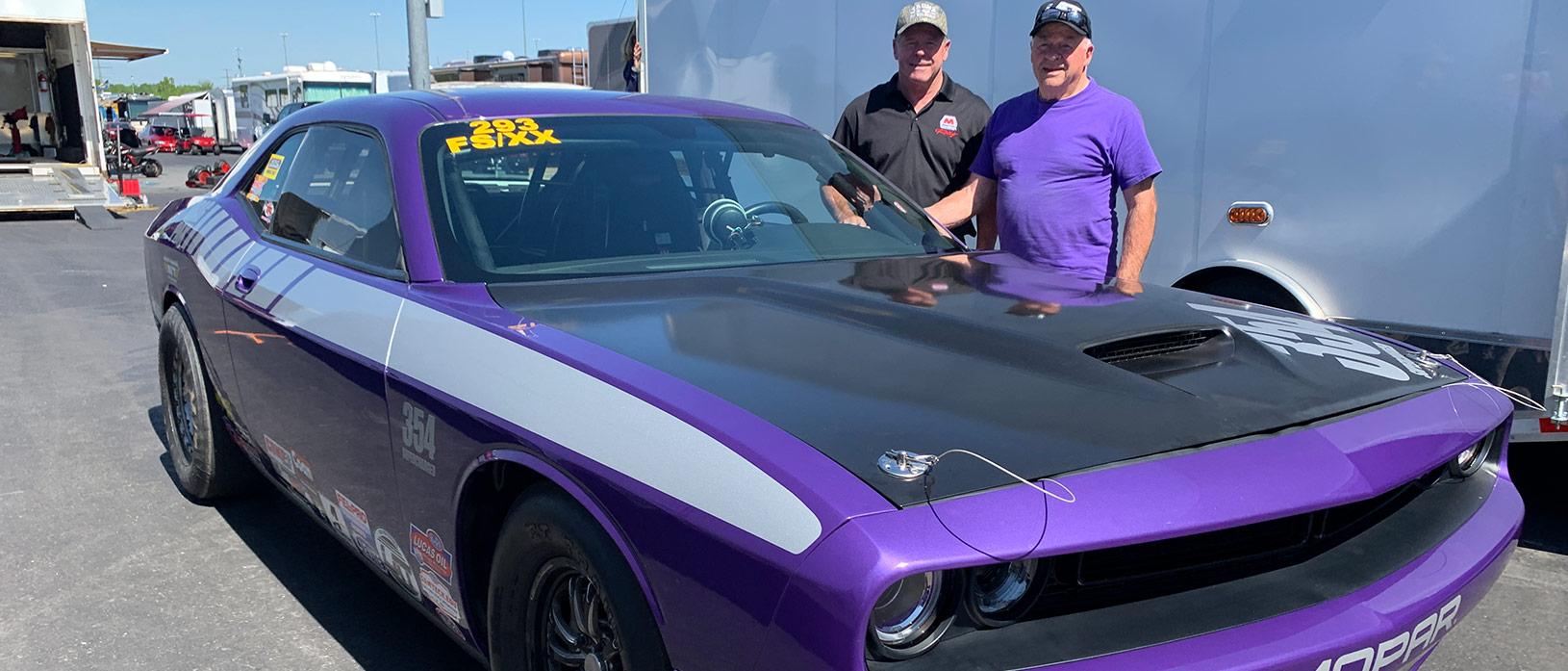 Two men posing next to purple challenger.