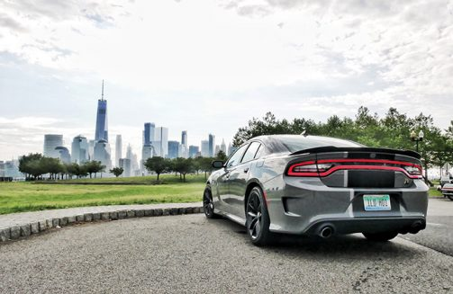 a gray dodge charger facing the new work city skyline
