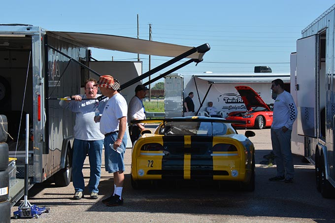 four men standing around a yellow dodge viper