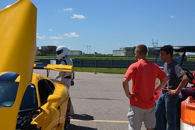 two men watching a driver in an all white race suit walk around his yellow dodge viper