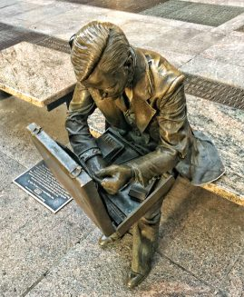 a bronze statue of a man with a briefcase