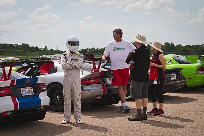 four people standing next to a line of dodge vipers