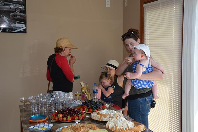 two women and three children eating food at a table
