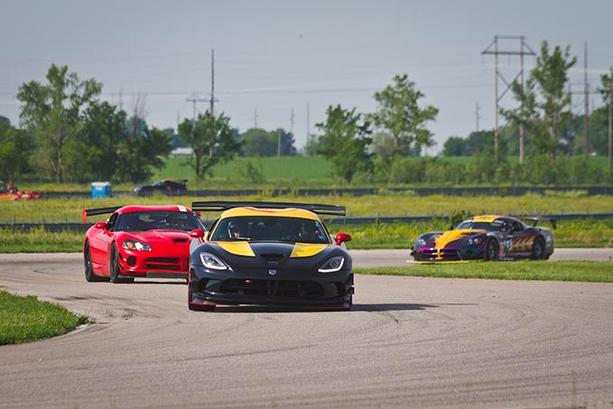 three dodge vipers driving around a race track