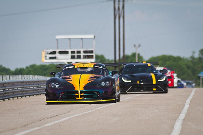 a line of dodge vipers driving around a race track