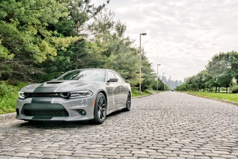 a dodge charger parked on a cobblestone road