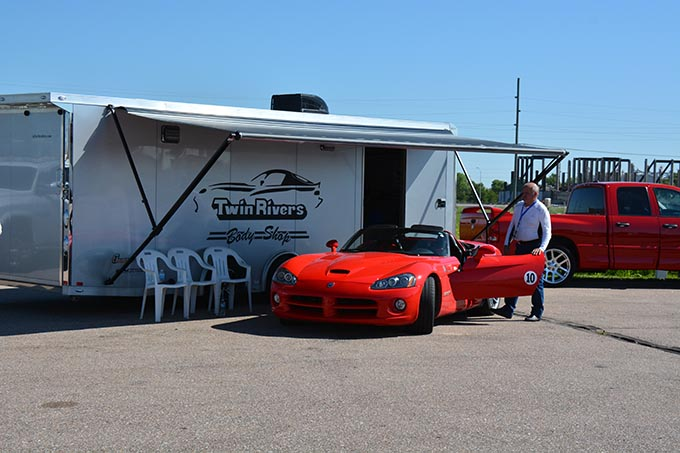 a man standing next to a red dodge viper