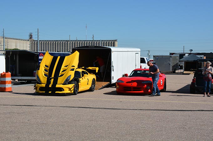 a red viper dodge viper parked next to a yellow dodge viper that has its hood open
