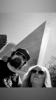 a man and woman with a city building behind them