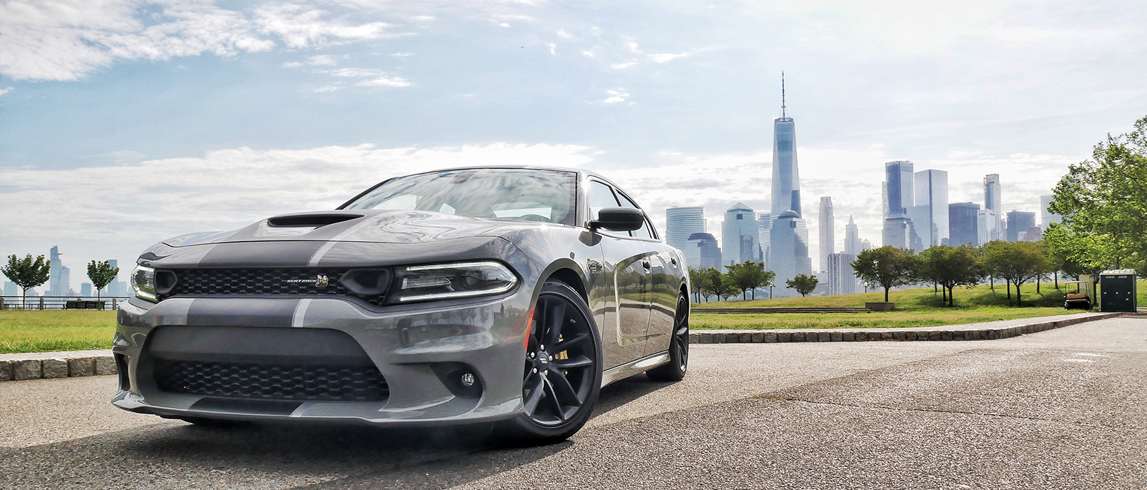 a gray dodge charger with the new york city skyline in the background