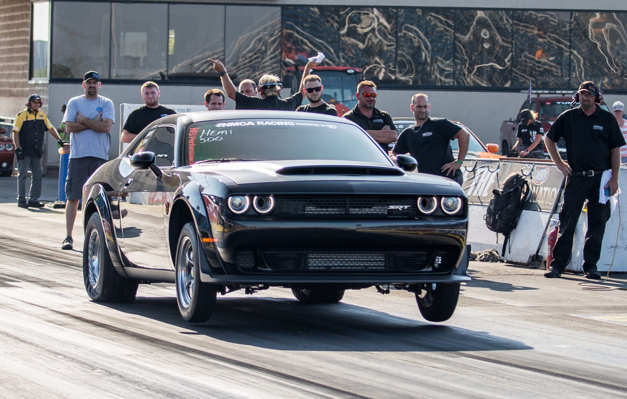 dodge vehicle on two wheels at the starting line of a drag strip