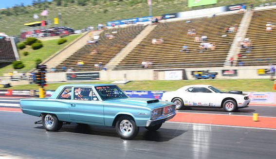 blue vehicle on the starting line of a drag strip