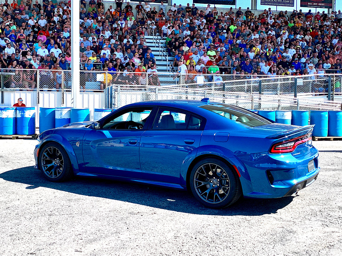 crowd sitting in bleachers watching a 2020 Charger Hellcat Widebody