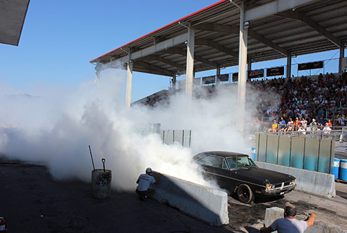 vehicle doing a burnout in a grand stand