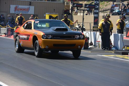 orange vehicle on the starting line of a drag strip