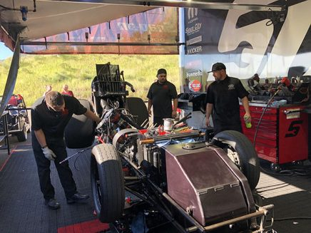 crew members working on cruz pedregon's funny car