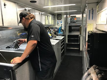 a crew member working with tools and vehicle parts inside ron capps' trailer