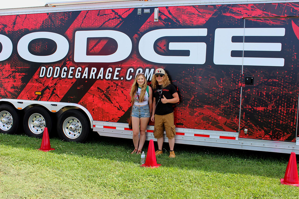 man and woman standing in front of a dodge trailer