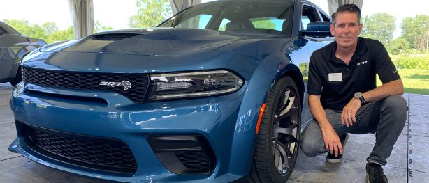 man kneeling next to a 2020 Charger Hellcat Widebody