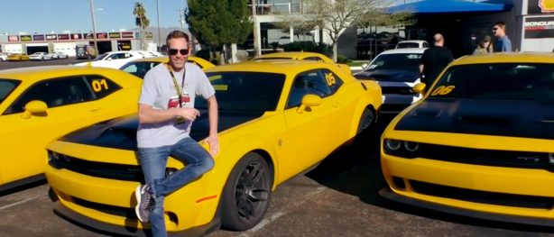 Man sitting on the hood of a yellow Dodge Challenger SRT Hellcat