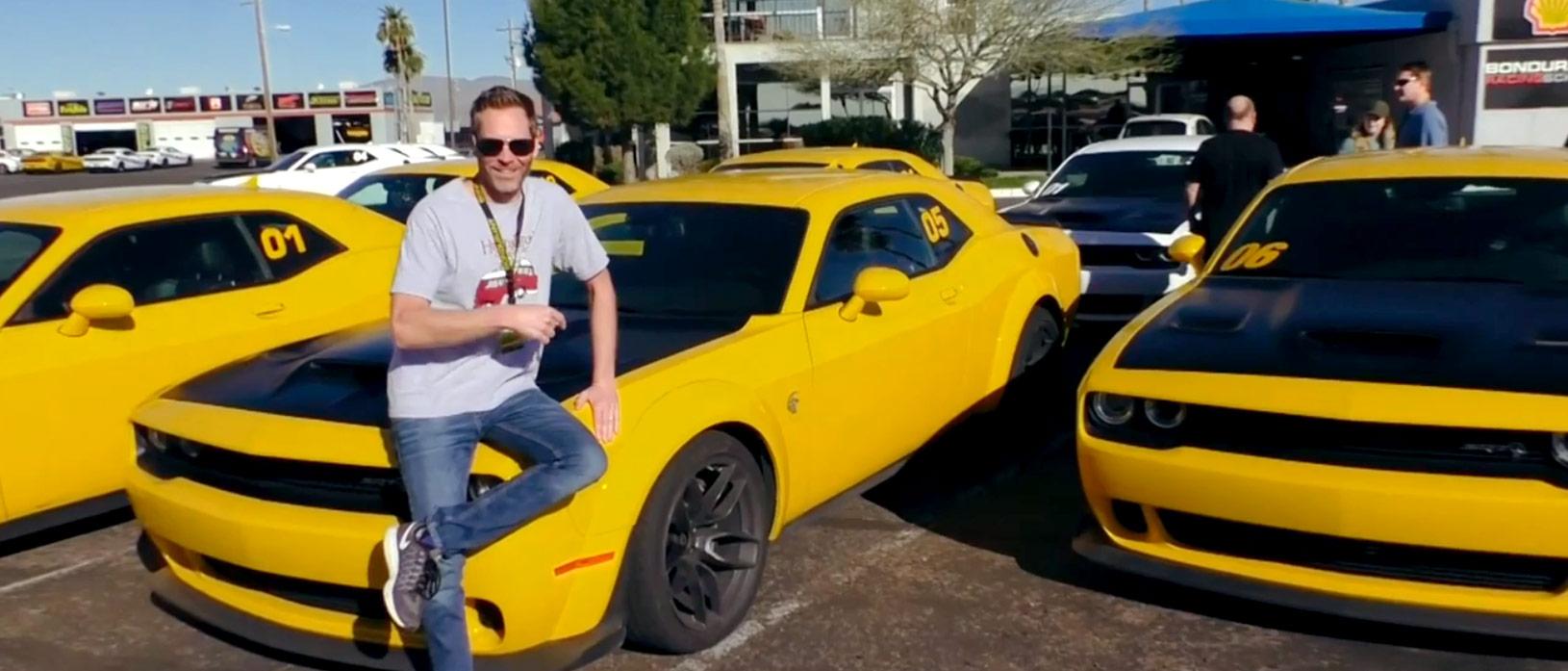Man sitting on the hood of a yellow Dodge Challenger SRT Hellcat