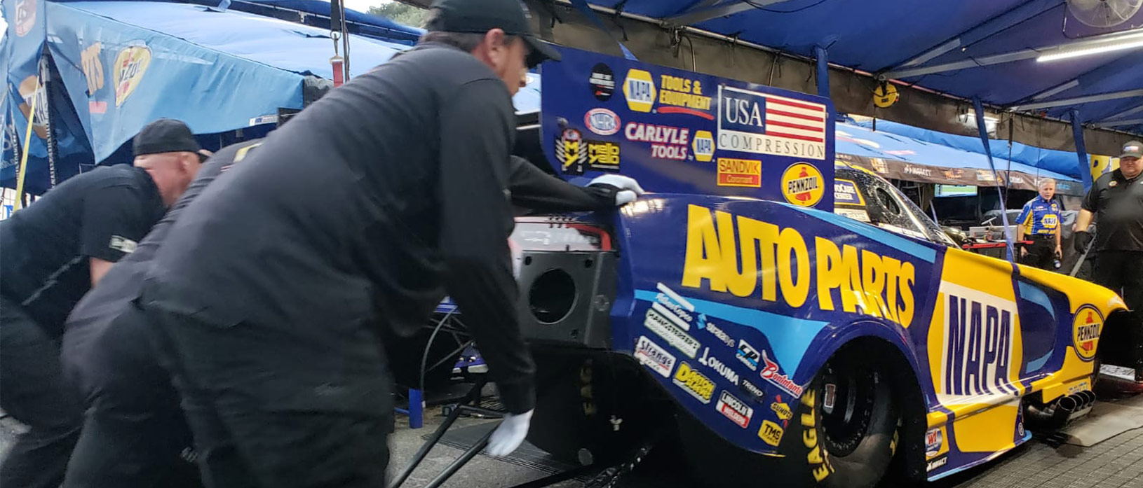 crew members pushing ron capps' funny car