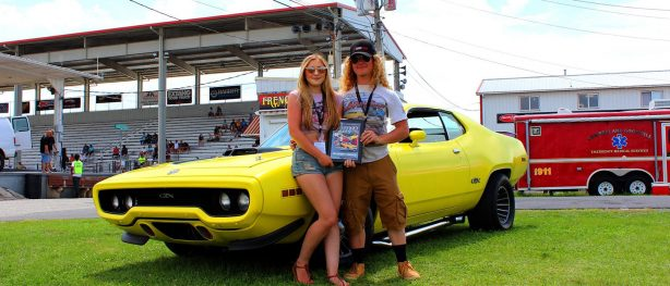 man and woman next to yellow 1971 Plymouth GTX