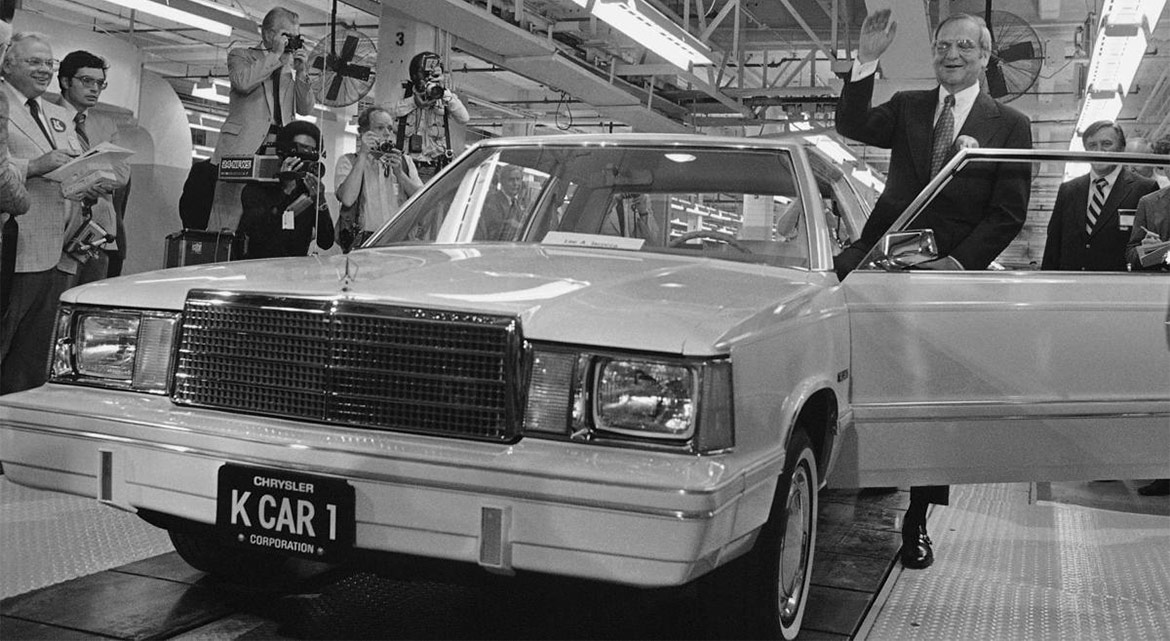 lee iococca standing in front of a car coming off the end of an assembly line