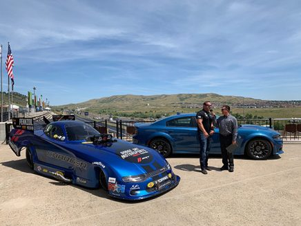 two men standing by a 2020 dodge charger srt hellcat widebody funny car
