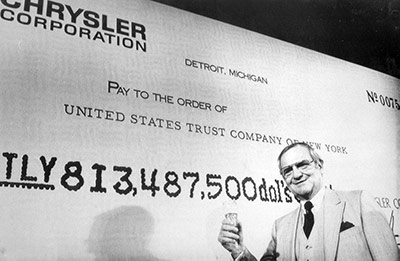 lee iacocca standing in front of a picture of a check
