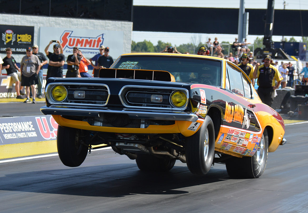 dodge vehicle on two wheels racing down a drag strip
