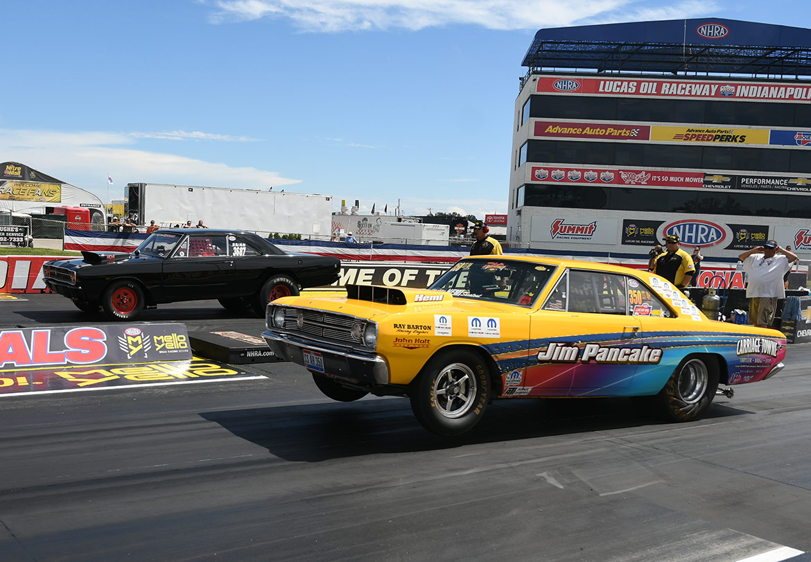two dodge vehicles at the starting line of a drag strip