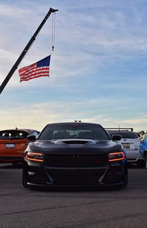dodge vehicles parked outside with an american flag hanging over them