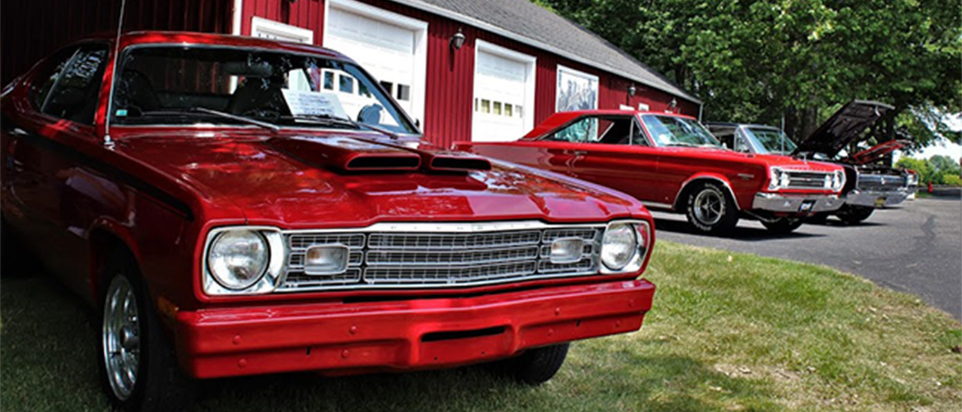 red cars parked outside next to a red barn