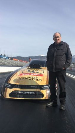 man standing next to a funny car