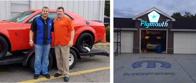 two men standing next to a mopar vehicle and a mopar garage